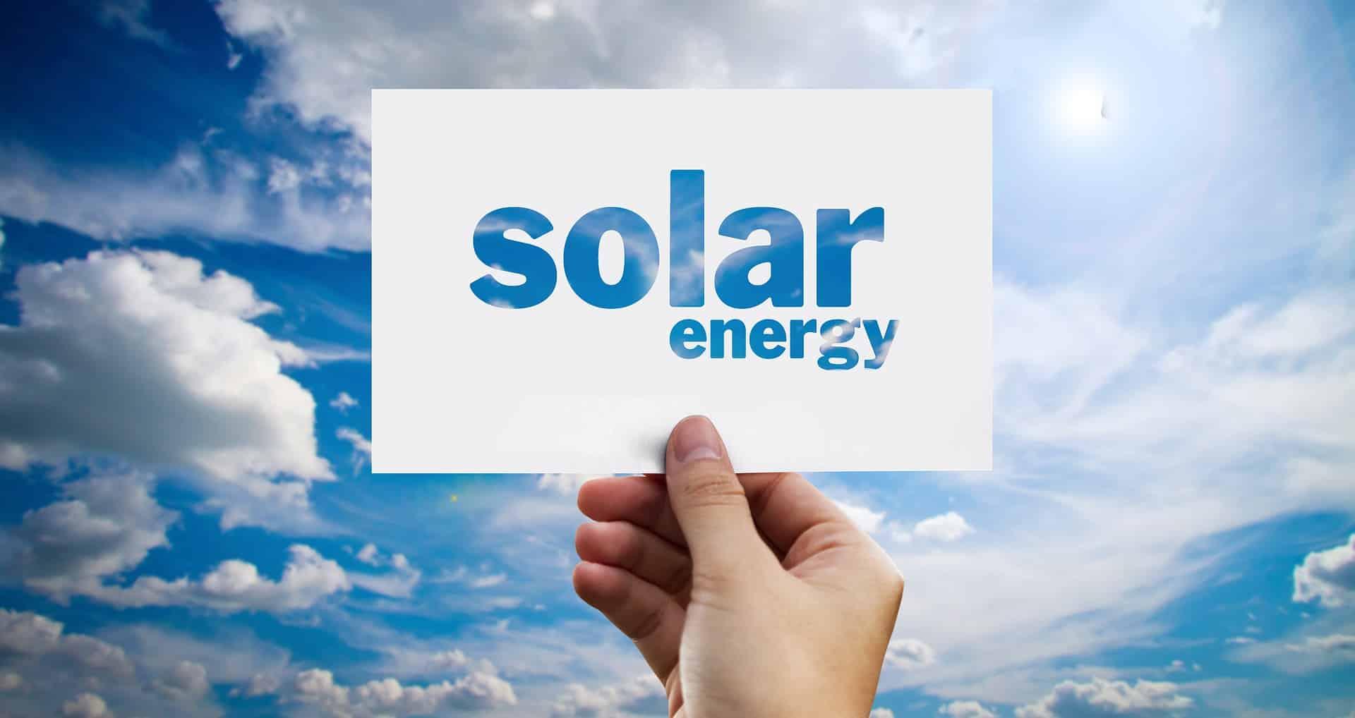 En hånd der holder et skilt, hvor der står solar energy på en blå himmel med lidt skyer
